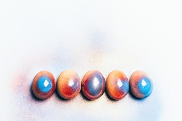 Cinque uova lucide colorate su uno sfondo bianco