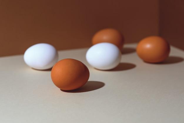 Cinque uova marroni e bianche con un'ombra dura. sono nell'angolo della scatola.