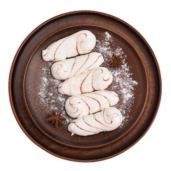 Cinque zefiri bianchi oblunghi spolverati di zucchero a velo. piatto di argilla con marshmallow isolato su sfondo bianco. la vista dall'alto.