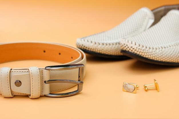 Cintura da uomo, scarpe, gemelli su fondo beige.