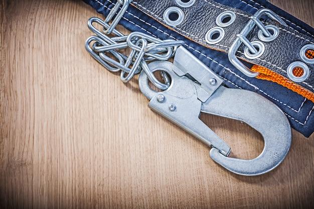 Cintura di costruzione con catena di moschettoni in metallo su tavola di legno