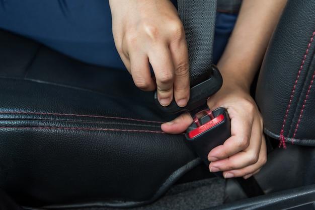 Cintura di sicurezza per auto. la donna allaccia la cintura di sicurezza dell'auto guida sicura. cintura di sicurezza in mano.