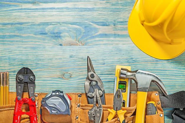 Cintura portautensili in pelle con lavorazione di costruzione su tavola orizzontale in legno