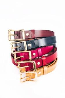 Cinture multicolori. molte cinture di cuoio su un bianco. cinture rosse, gialle, blu, marroni, verdi sono scolpite su un bianco