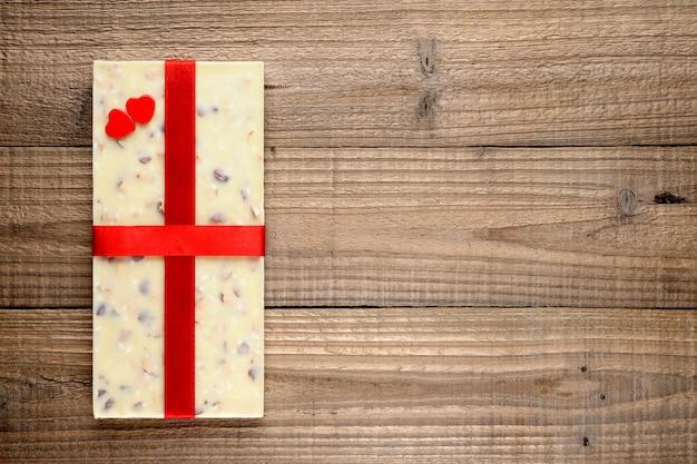 Cioccolata bianca con il nastro e due cuori rossi su fondo di legno
