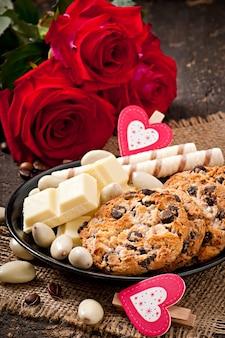 Cioccolata bianca, mandorle e biscotti su una superficie di legno