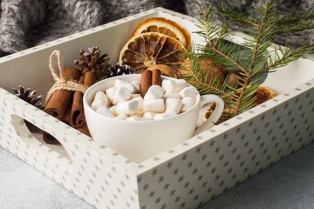 Cioccolata calda con bastoncini di cannella marshmallow, anice e noci sul vassoio di legno