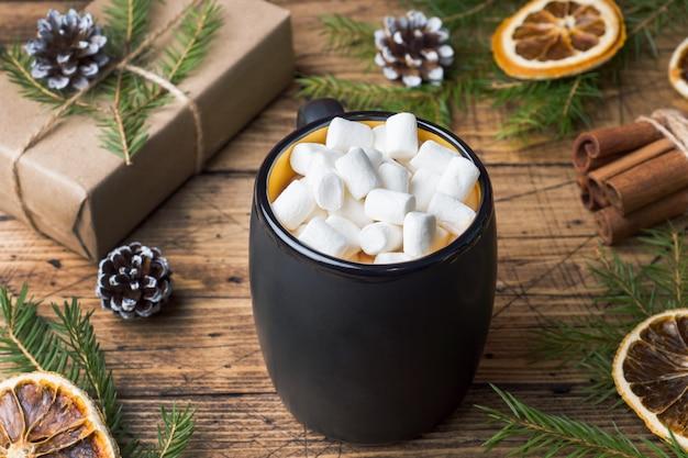 Cioccolata calda con bastoncini di cannella marshmallow, anice, noci su legno