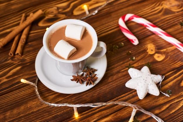 Cioccolata calda con caramelle gommosa e molle sul tavolo di legno a natale
