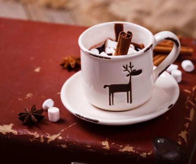 Cioccolata calda con caramelle marshmallow. bevanda calda per le vacanze con bastoncini di cannella. caldo natale. natura morta invernale nella coppa.