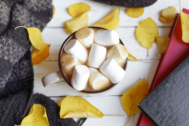 Cioccolata calda con caramelle marsmallow, foglie di autunno