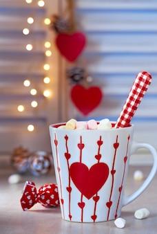 Cioccolata calda con marshmallow, cuore rosso sulla coppa, parete invernale con luci sfuocate