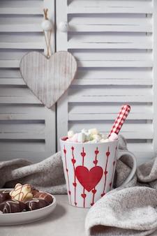 Cioccolata calda con marshmallow, cuore rosso sulla tazza sul tavolo con decorazioni invernali
