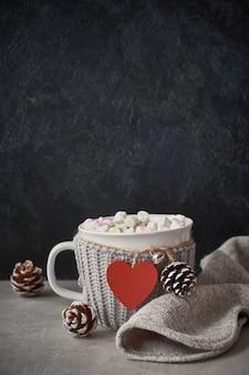 Cioccolata calda con marshmallow, cuore rosso sulla tazza sul tavolo con pigne, copia-spazio