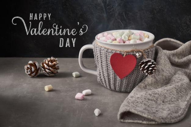 Cioccolata calda con marshmallow, cuore rosso sulla tazza sul tavolo