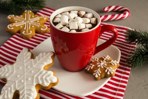Cioccolata calda con marshmallow nella tazza rossa e biscotti di natale