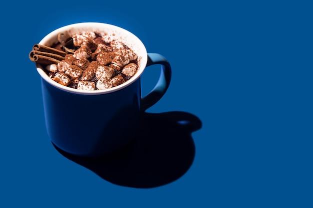 Cioccolata calda di natale in una tazza blu su sfondo blu.