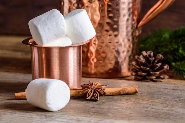Cioccolata calda fatta in casa con marshmallow in una tazza di rame