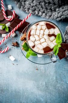 Cioccolata calda fatta in casa con menta, bastoncino di zucchero e marshmallow
