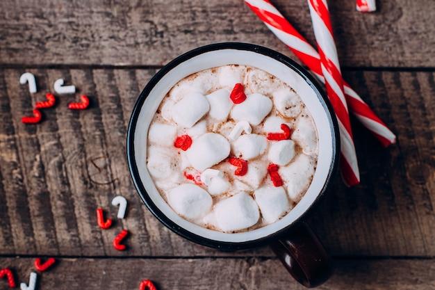 Cioccolata calda, marshmallow e bastoncino di zucchero. tradizionale bevanda natalizia invernale.