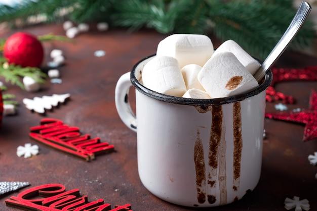 Cioccolata calda o cacao con marshmallow e spezie su sfondo scuro di pietra.