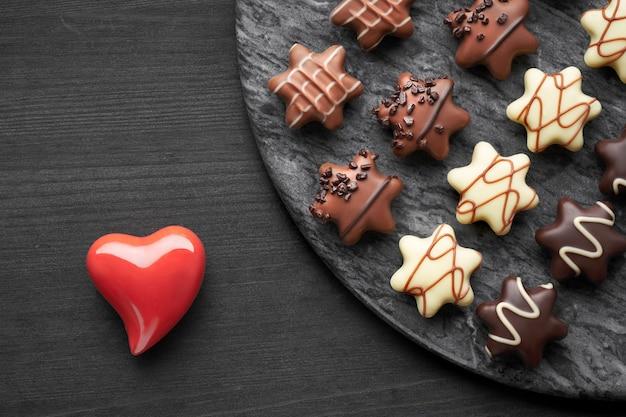 Cioccolatini a forma di stella su superficie scura strutturata con heari in ceramica rossa