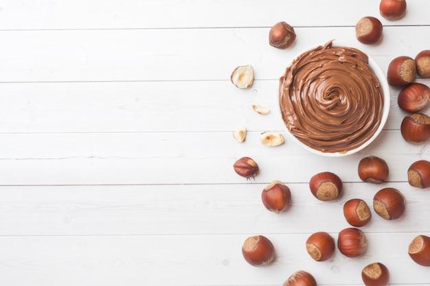 Cioccolato al dado torrone in un piatto su uno sfondo bianco con noci nocciole.