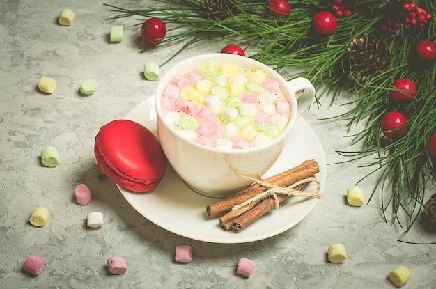 Cioccolato con bastoncini di cannella, marshmallow, amaretto e polvere di cacao, retro in cemento grigio