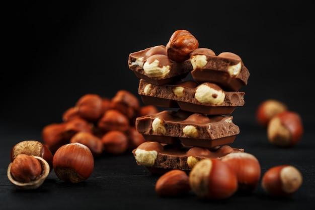 Cioccolato con nocciole a forma di torre su uno sfondo scuro, circondato da noci nel guscio e sbucciato.