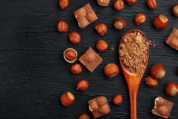 Cioccolato con nocciole e un cucchiaio di legno con cacao, circondato da noci nel guscio e sbucciato.