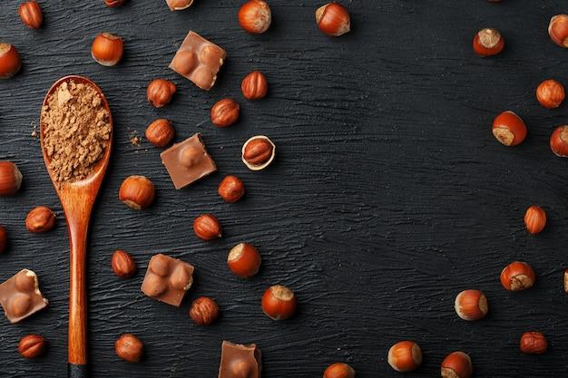 Cioccolato con nocciole e un cucchiaio di legno con cacao su uno sfondo scuro, circondato da noci nel guscio e sbucciato.
