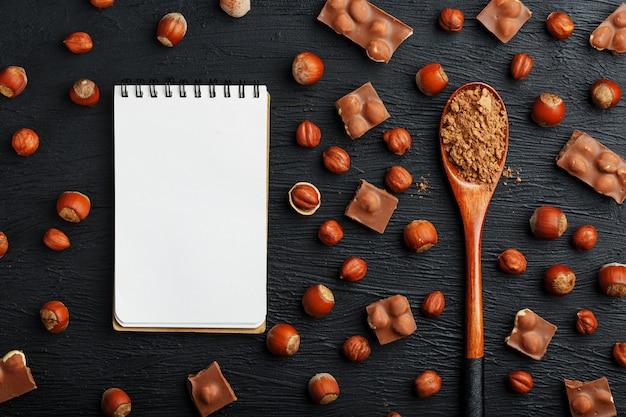 Cioccolato con nocciole, un quaderno con pagine bianche e un cucchiaio di legno con cacao, circondato da noci nel guscio e pelato.