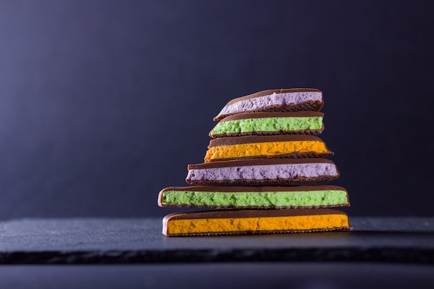 Cioccolato con ripieno di frutta. fette di cioccolato con mirtilli, menta e arancia. cioccolato fondente su lavagna