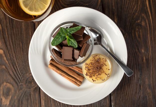 Cioccolato e miele su un piatto vicino a rotoli di cannella