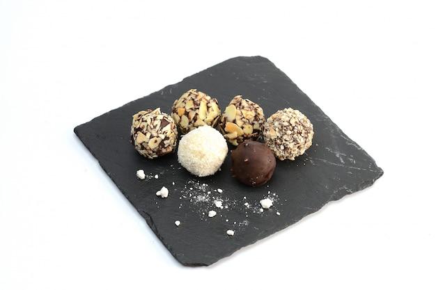 Cioccolato fatto a mano assortito sul bordo di pietra nero, su bianco
