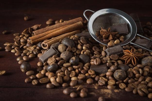 Cioccolato fondente, spezie, chicchi di caffè e colino metallico su una superficie di legno