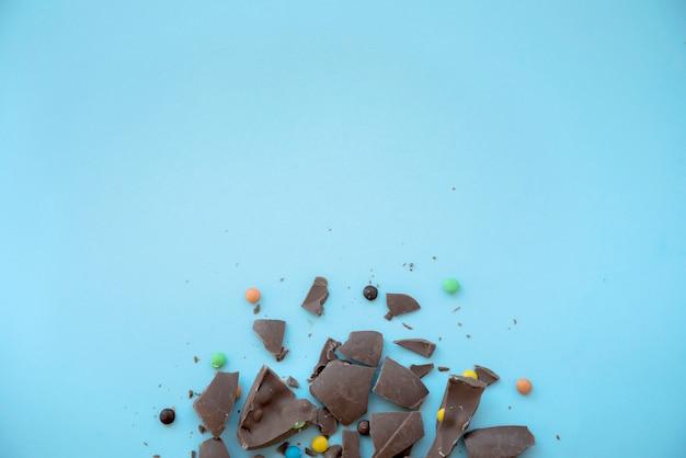 Cioccolato incrinato con caramelle sul tavolo blu