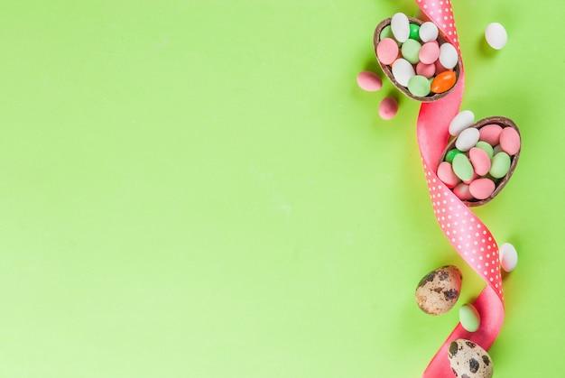 Cioccolato uovo di pasqua, uova di caramella, uova di quaglia e nastro festivo