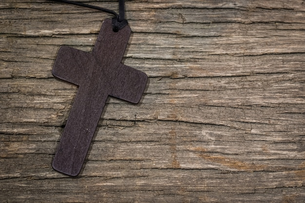 Ciondolo croce sul tavolo di legno con spazio di copia