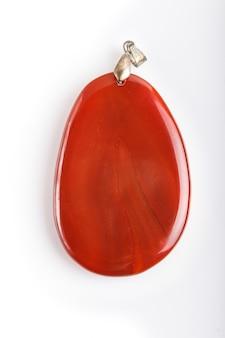 Ciondolo in onice rosso isolato su superficie bianca