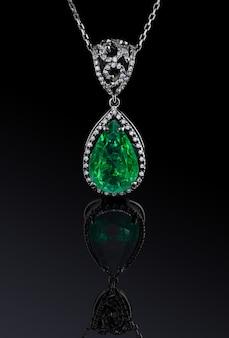 Ciondolo in oro bianco di lusso con grande smeraldo verde naturale e diamanti isolati su sfondo nero con riflessione, percorso di clipping incluso. estremo da vicino.