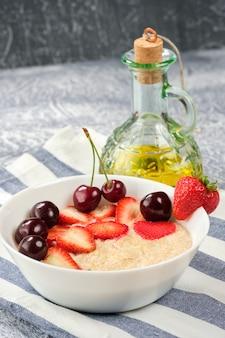 Ciotola bianca con farina d'avena e fragole e ciliegie e olio d'oliva su un tovagliolo a strisce