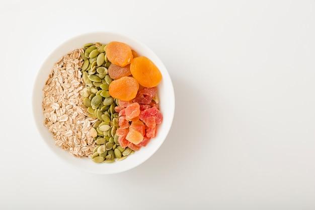 Ciotola bianca di muesli, semi di zucca e frutta secca sopra lo sfondo bianco