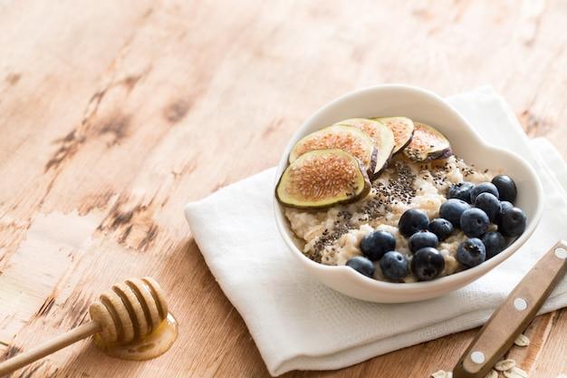 Ciotola bianca di porridge di avena con fichi, mirtilli e semi di chia.