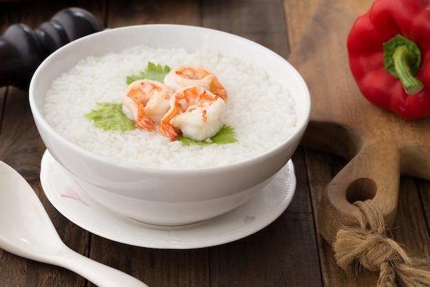 Ciotola bianca di porridge di gamberetti, zuppa di riso tailandese con gamberi (khao tom koong) su legno