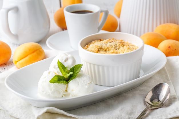 Ciotola con briciola croccante di albicocche e gelato sul tavolo