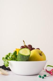 Ciotola con cetriolo e mela deliziosa sul tavolo