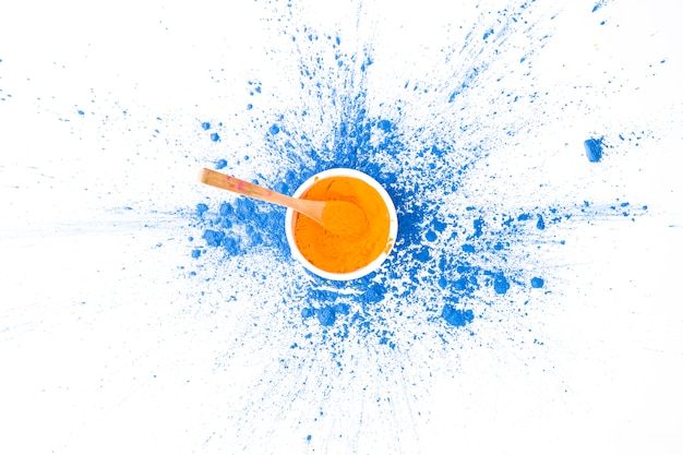 Ciotola con cucchiaio e colore arancione su colori blu asciutti