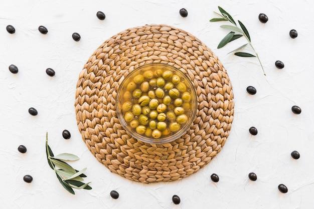 Ciotola con olive e olio su corsetto con fondale bianco