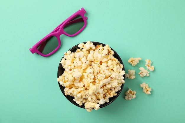 Ciotola con popcorn e occhiali 3d sulla menta, vista dall'alto